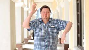Hombre gordo joven alegre que hace los ejercicios o el baile divertidos al aire libre metrajes