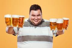 Hombre gordo joven en la cerveza más oktoberfest, de consumición en fondo amarillo Foto de archivo libre de regalías