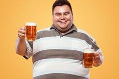 Hombre gordo joven en la cerveza más oktoberfest, de consumición en fondo amarillo Fotos de archivo libres de regalías