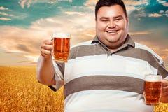 Hombre gordo joven en la cerveza más oktoberfest, de consumición en fondo amarillo Fotografía de archivo