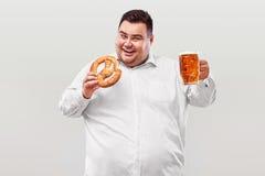 Hombre gordo joven en la cerveza más oktoberfest, de consumición y el pretzel de la consumición aislados en el fondo blanco Fotos de archivo libres de regalías