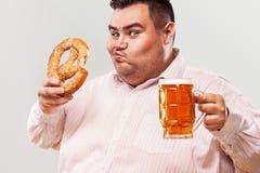 Hombre gordo joven en la cerveza más oktoberfest, de consumición y el pretzel de la consumición aislados en el fondo blanco Imagen de archivo libre de regalías