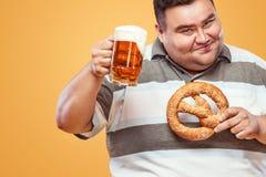 Hombre gordo joven en la cerveza y el pretzel más oktoberfest, de consumiciones de la consumición en fondo amarillo Foto de archivo