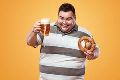 Hombre gordo joven en la cerveza y el pretzel más oktoberfest, de consumiciones de la consumición en fondo amarillo Imagenes de archivo