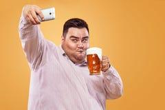 Hombre gordo joven en la más oktoberfest con la cerveza en el fondo amarillo que hace la foto del selfie en smartphone Imagenes de archivo