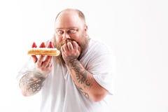 Hombre gordo muerto de hambre que mira fijamente el postre mouthwatering fotos de archivo