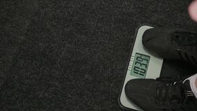 Hombre gordo pesado en las escalas en el gimnasio almacen de video