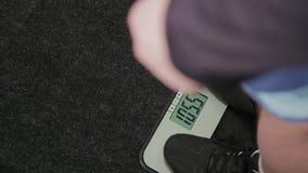 Hombre gordo pesado en las escalas en el gimnasio metrajes