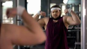 Hombre gordo positivo que mira la reflexión de espejo y que presenta, fingimiento muscular foto de archivo libre de regalías