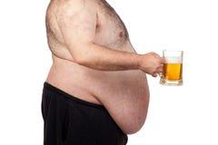 Hombre gordo que bebe un tarro de cerveza Imagenes de archivo
