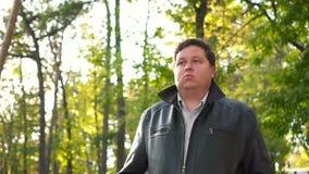 Hombre gordo que camina en el rastro en un parque almacen de metraje de vídeo