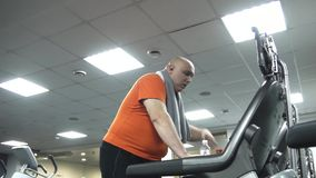 Hombre gordo que camina en la rueda de ardilla, limpiando su cabeza con una toalla