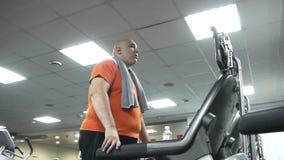 Hombre gordo que comienza a ir en la rueda de ardilla Visión inferior