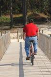 Hombre gordo que completa un ciclo en la playa Foto de archivo