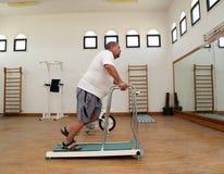 Hombre gordo que corre en la rueda de ardilla del instructor Imagen de archivo