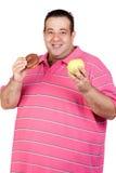 Hombre gordo que decide entre un caramelo y una manzana Imagen de archivo