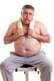 Hombre gordo que descansa sobre un banco para los abdominals, cansado después del tr Imagen de archivo