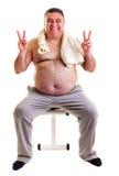 Hombre gordo que descansa sobre un banco para los abdominals y que muestra Vic Fotografía de archivo
