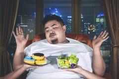 Hombre gordo que elige las comidas con la expresión confusa fotos de archivo