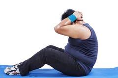 Hombre gordo que hace abdominales Imagen de archivo