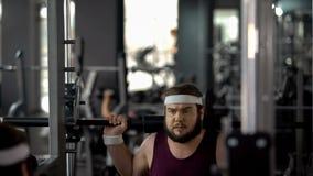 Hombre gordo que hace apenas el ejercicio con el barbell en gimnasio, entrenamiento de la aptitud, pérdida de peso imagenes de archivo