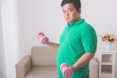 Hombre gordo que hace ejercicio en casa, levantando encima de una pesa de gimnasia en Imágenes de archivo libres de regalías
