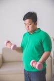 Hombre gordo que hace ejercicio en casa, levantando encima de una pesa de gimnasia en Foto de archivo