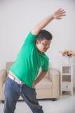 Hombre gordo que hace un cierto ejercicio en casa Imagen de archivo