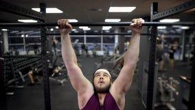 Hombre gordo que intenta levantar en barra de deporte en deseo del gimnasio de perder el peso adicional fotos de archivo libres de regalías