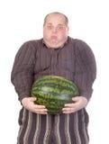 Hombre gordo que lucha para sostener la sandía Imagen de archivo