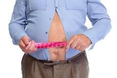 Hombre gordo que mide su stomack grande Fotografía de archivo