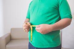 Hombre gordo que mide su vientre en casa Fotografía de archivo libre de regalías