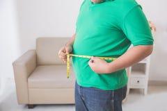 Hombre gordo que mide su vientre en casa Fotos de archivo libres de regalías
