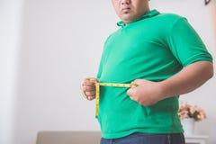 Hombre gordo que mide su vientre en casa Imagen de archivo libre de regalías