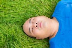 Hombre gordo que miente en la hierba verde para relajarse Foto de archivo