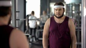 Hombre gordo que mira la reflexión de espejo en gimnasio, entrenamiento mental antes del entrenamiento fotos de archivo libres de regalías