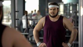 Hombre gordo que parece decepcionado debido a mún resultado después de entrenamientos de la pérdida de peso imagen de archivo libre de regalías