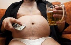 Hombre gordo que se sienta en el sofá Imagen de archivo