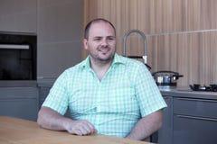 Hombre gordo que se sienta en la tabla y las sonrisas de cocina fotos de archivo