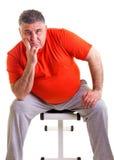 Hombre gordo que se sienta en un banco para los abdominals, él toma un bre Imagen de archivo libre de regalías
