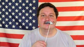 Hombre gordo que sostiene un palillo con el bigote falso debajo de su nariz y que mira la cámara almacen de video