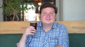 Hombre gordo que sostiene un vidrio de cola del refresco carbonatado, sentándose en café Bebida y sano almacen de video