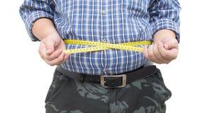 Hombre gordo que sostiene una cinta de la medida aislada Foto de archivo