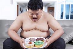 Hombre gordo que sostiene una placa de anillos de espuma Fotografía de archivo