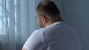 Hombre gordo que sufre del dolor de cuello, dando masajes a mano, efecto sedentario del trabajo almacen de video
