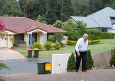Hombre gordo que tiene una dificultad que camina encima de una calzada extremadamente escarpada con las casas de la vecindad en e imagenes de archivo