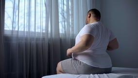 Hombre gordo tosco que estira los músculos por mañana en la cama, sufriendo de dolor de espalda foto de archivo