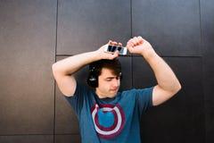 Hombre graciosamente joven en los auriculares y con el teléfono en sus manos que bailan contra la perspectiva de una pared gris Imagen de archivo