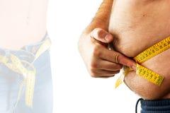Hombre grande que mide su vientre con una cinta métrica Fotos de archivo