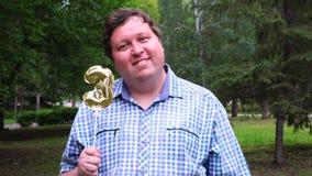 Hombre grande que sostiene el globo de oro que hace el número 3 al aire libre 3o partido de la celebración del aniversario almacen de video